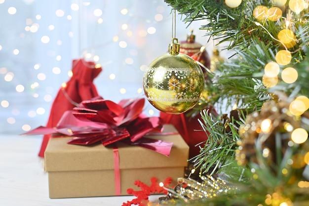 Cadeaux et surprises de noël sur une table en bois blanche à côté des branches d'un arbre de noël