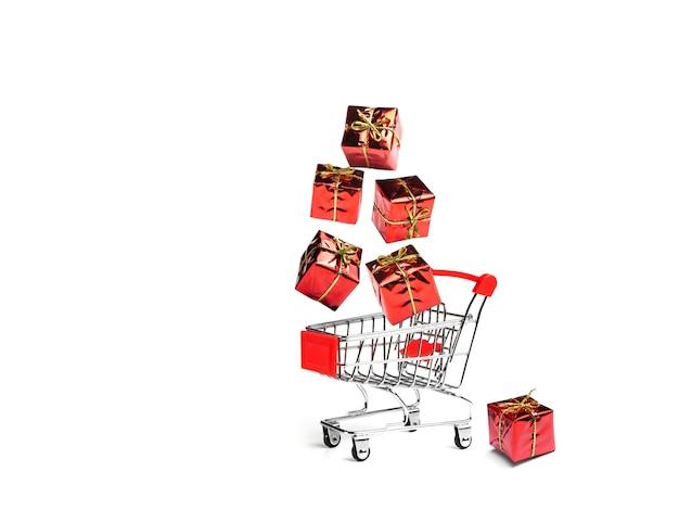 Les cadeaux tombent dans le panier de l'acheteur. panier complet. le concept de cadeaux et d'achats avant la nouvelle année.