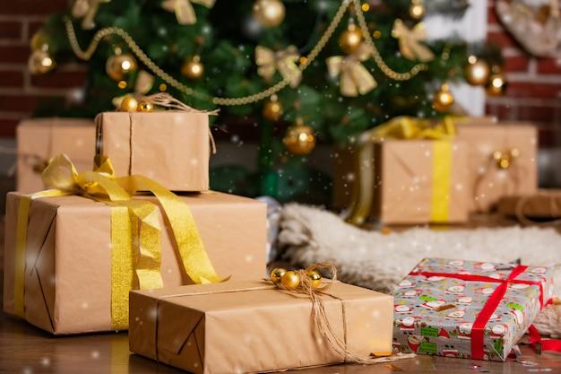 Des cadeaux tout faits du nouvel an dans différentes boîtes pour toute la famille sont près du sapin de noël dans la chambre en hiver