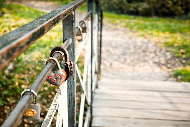 Cadenas d'amour rouillé en forme de coeur accroché sur rail de pont en bois