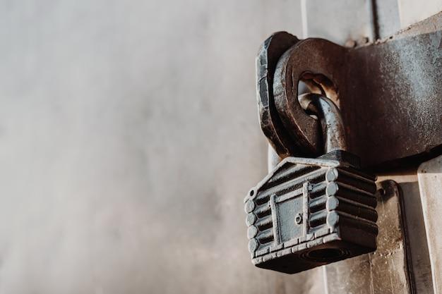 Un cadenas en forme de cabane est suspendu aux charnières du portail fermé. portes métalliques.