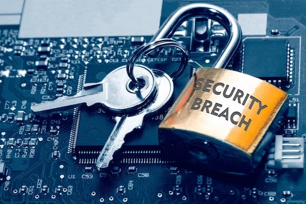 Cadenas avec l'inscription une violation de la sécurité et les clés sur le pcb. concept de sécurité informatique et de protection du réseau internet.