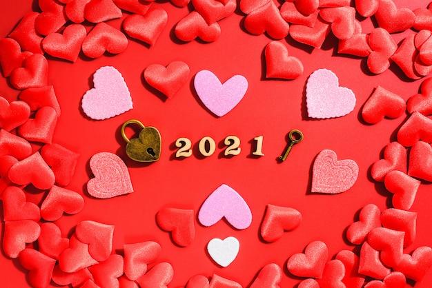 Un cadenas représente l'engagement amoureux d'un couple en 2021, sur fond rouge avec des coeurs pour la saint valentin.