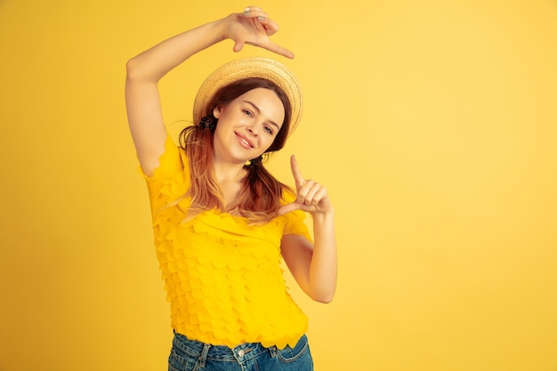 Cadrage, selfie, souriant. portrait de femme caucasienne sur fond de studio jaune. beau modèle féminin au chapeau. concept d'émotions humaines, expression faciale, ventes, publicité. l'été, les voyages, la station balnéaire.