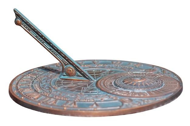 Cadran solaire antique avec un beau cadran et ornement isolé sur fond blanc. le disque en bronze oxydé. mise au point sélective peu profonde sur le centre du disque.