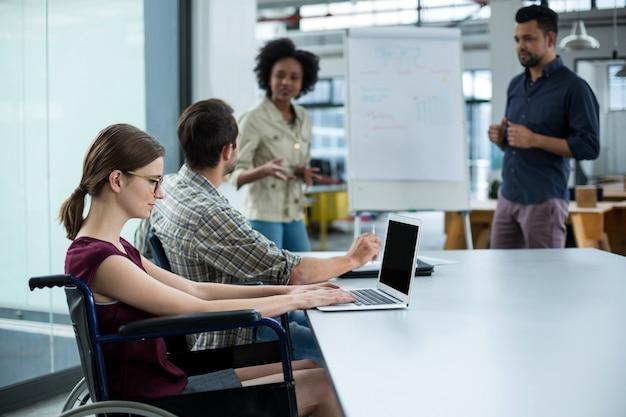 Cadre d'affaires handicapé en fauteuil roulant travaillant sur ordinateur portable en réunion