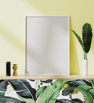 Cadre d'affiche blanc blanc maquette dans un intérieur de style tropical avec mur jaune, impression de feuilles tropicales, rendu 3d