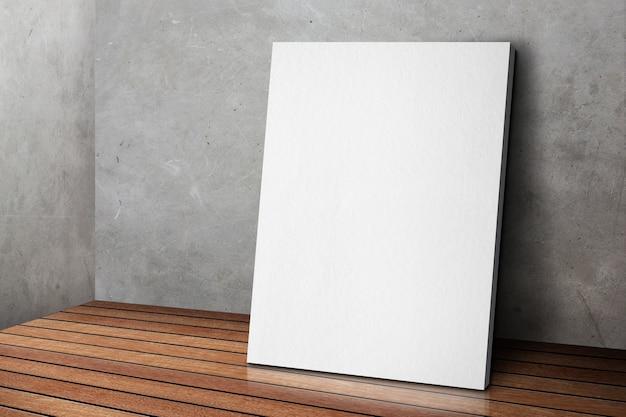 Cadre affiche blanc blanc se penchant au mur de béton gris grunge