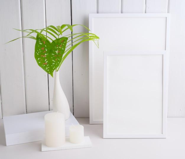 Cadre d'affiche simulé et feuilles de palmier plante tropicale botanique dans un beau vase en céramique blanche sur fond de mur de table blanc