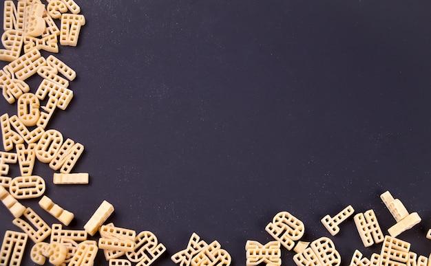 Cadre d'alphabet macaronis bruts sur fond noir