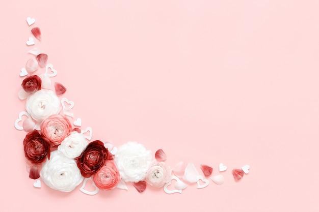 Cadre d'angle fait de fleurs de renoncule, de pétales et de coeurs sur une vue de dessus rose clair