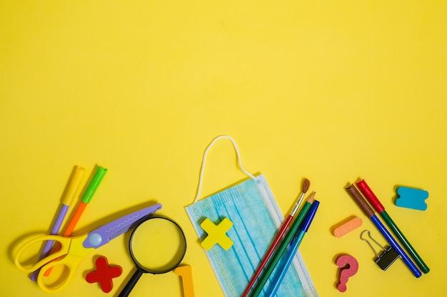 Cadre avec des articles scolaires et un masque sur le bord de l'arrière-plan