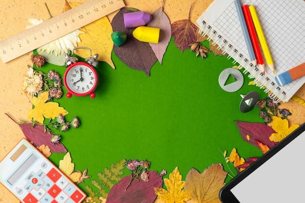 Cadre d'automne de feuilles sèches et de fournitures scolaires.