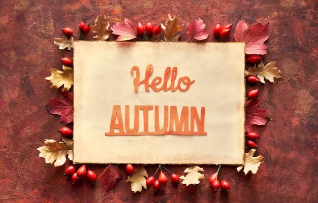 Cadre d'automne rouge et marron avec bordure décorative de feuilles d'automne de chêne. texte fait à la main bonjour l'automne sur la page de papier vieilli.