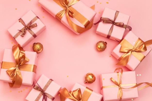 Cadre de bannière de noël ou du nouvel an avec des boules d'or, des coffrets cadeaux en papier rose décorés de rubans dorés brillants sur un rose.