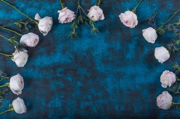 Cadre de belles fleurs avec des roses sur fond bleu