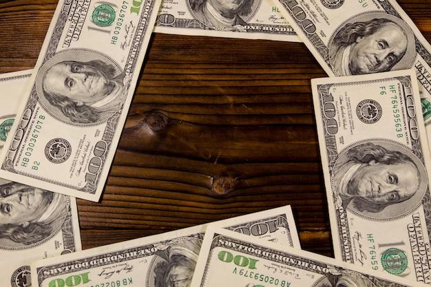 Cadre de billets de cent dollars sur fond de bois