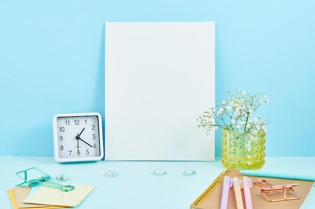 Cadre blanc blanc sur la table bleue contre le mur bleu, alarme, fleur en vaze.