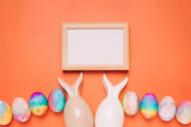 Cadre blanc en bois sur les deux oeufs de pâques avec des oreilles de lapins sur fond orange