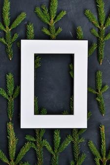 Cadre blanc sur les branches de sapin sur noir