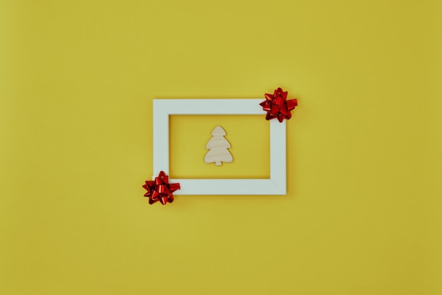 Cadre blanc avec des décorations de noël et un arbre de noël à l'intérieur sur fond jaune