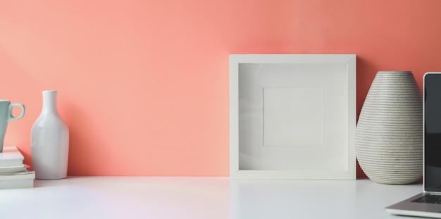 Cadre blanc sur l'espace de travail de bureau blanc