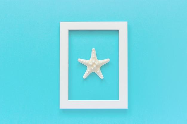 Cadre blanc avec étoile de mer sur fond bleu. modèle de vue de dessus plat créatif pour carte postale, conception espace de copie pour le texte