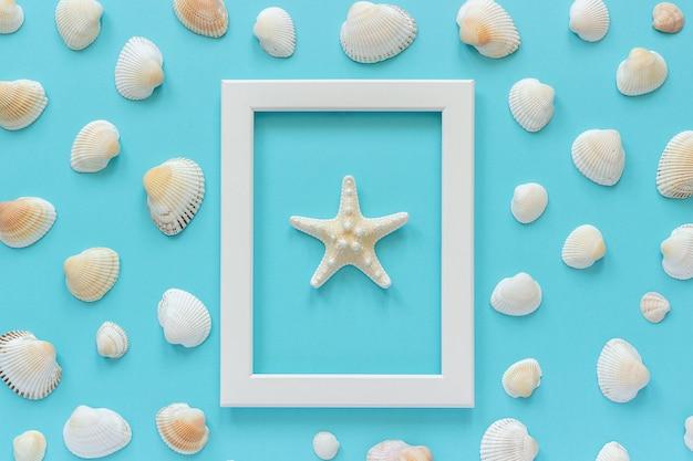 Cadre blanc d'étoiles de mer sur fond bleu et coquillages.