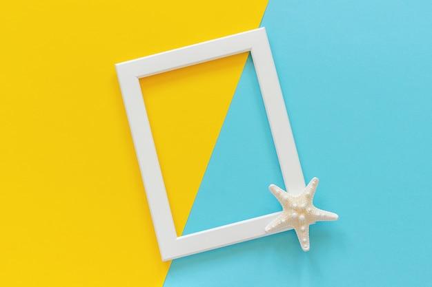 Cadre blanc d'étoiles de mer sur fond bleu et jaune.