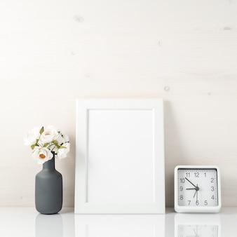 Cadre blanc, fleur dans un vase, horloge sur une table blanche contre le wh