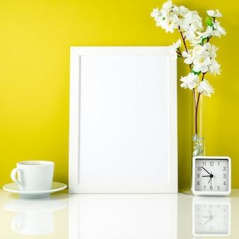 Cadre blanc, fleur dans un vase, tasse de thé ou de café, horloge