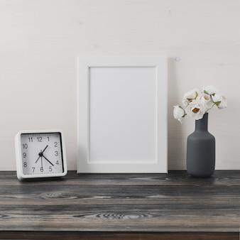 Cadre blanc, fleur en vaze, horloge sur une table en bois gris foncé contre le mur blanc