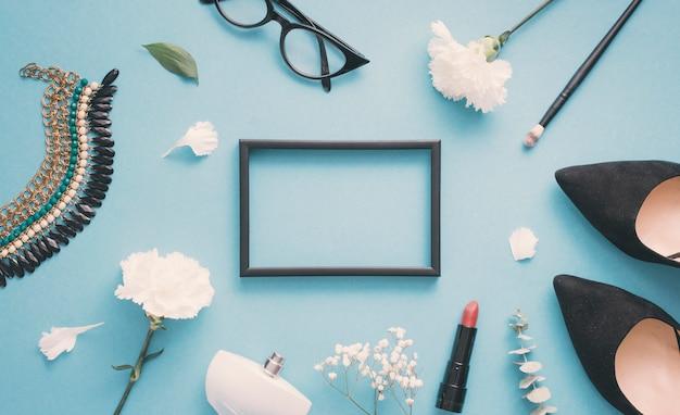 Cadre blanc avec des fleurs blanches, des chaussures de femme et des produits de beauté