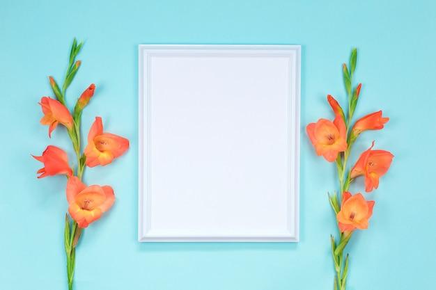 Cadre blanc avec des fleurs de glaïeul orange