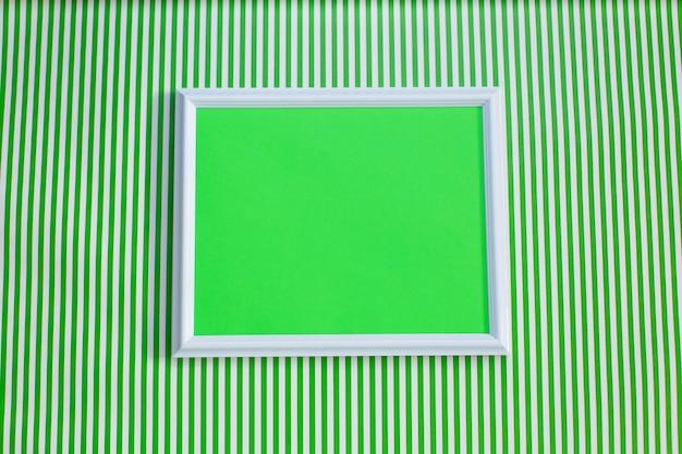 Cadre blanc avec un fond vert blanc sur un fond rayé vert et blanc