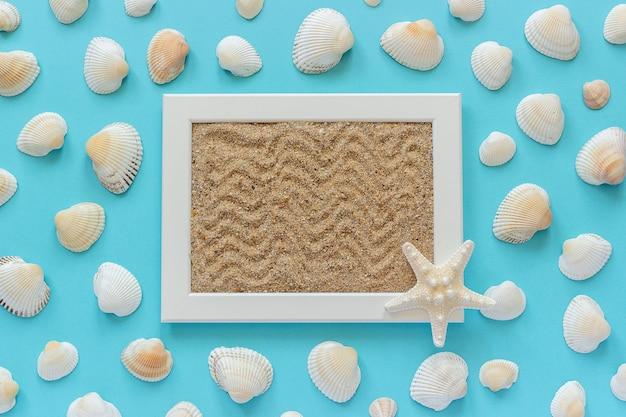 Cadre blanc avec sable de mer et étoile de mer, coquillages sur fond bleu