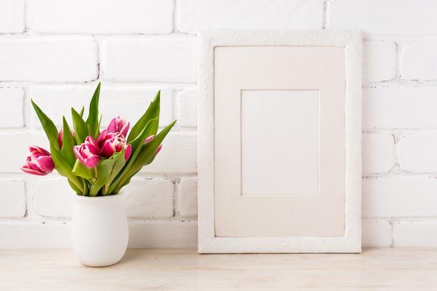 Cadre blanc avec tulipe rose magenta dans le pot de fleur