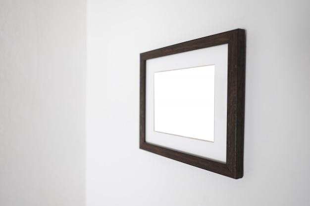 Cadre blanc vide sur un mur pour maquette