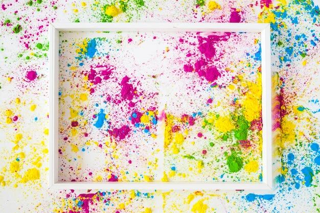 Un cadre blanc vide sur poudre de holi coloré sur fond blanc