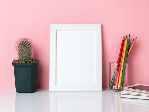 Cadre blanc vierge, crayon de couleur dans un bocal, plante cactus sur une table blanche contre le mur rose