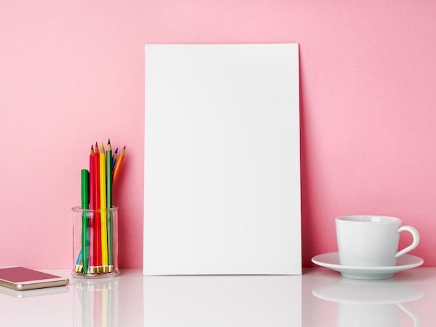 Cadre blanc vierge et crayon de couleur dans un bocal, tasse de café ou de thé sur une table blanche contre le mur rose