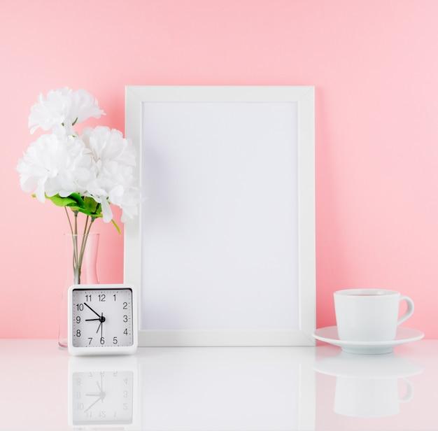 Cadre blanc vierge, fleur, horloge, tasse de café ou de thé sur une table blanche contre la copie du mur rose. .