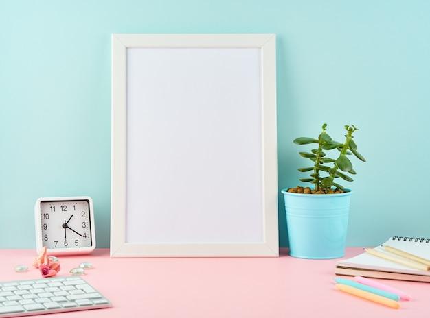 Cadre blanc vierge maquette, alarme, bloc-notes, tasse de café sur la table rose contre le mur bleu avec copie.