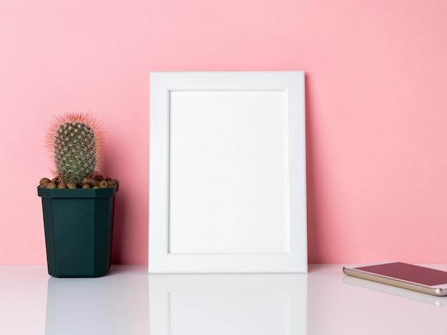 Cadre blanc vierge et plante cactus, sur une table blanche contre la copie du mur rose
