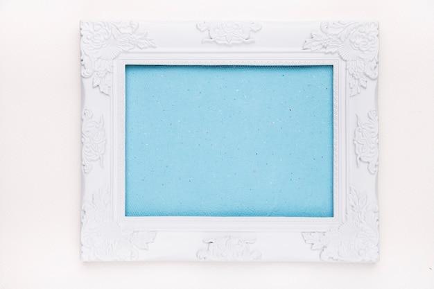 Cadre bleu avec une bordure en bois blanche isolée sur fond blanc