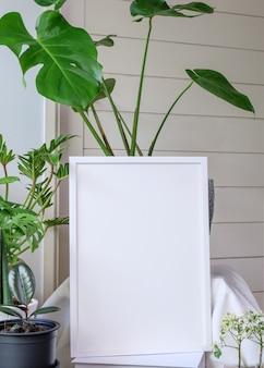 Cadre en bois d'affiche de maquette et plante tropicale botanique géante de monstera dans un beau pot en béton posé sur une table en bois dans un salon moderne élégant avec un mur blanc