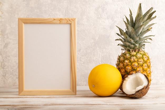 Cadre en bois avec ananas, melon, noix de coco sur fond de béton gris. vue latérale, copiez l'espace.