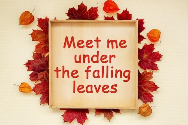 Cadre en bois d'automne avec texte, rencontrez-moi sous les feuilles qui tombent sur une planche de bois
