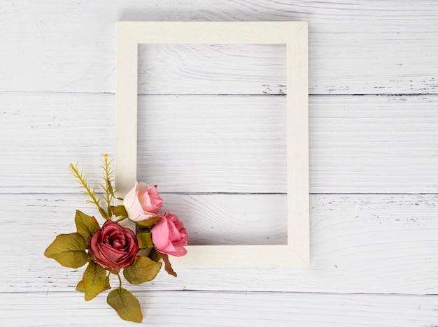Un cadre en bois blanc et un bouquet de fleurs