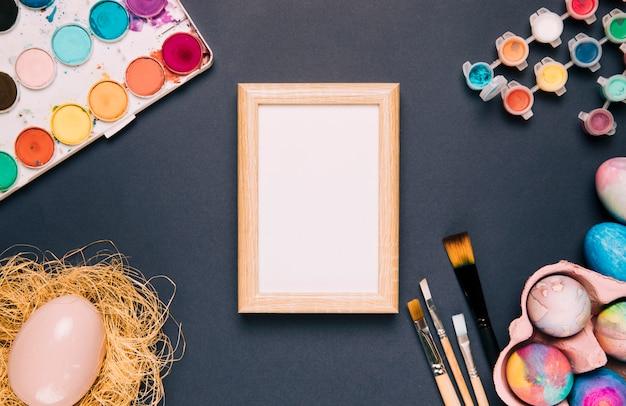 Cadre en bois blanc avec peinture à l'aquarelle; pinceaux et oeuf de pâques sur fond noir